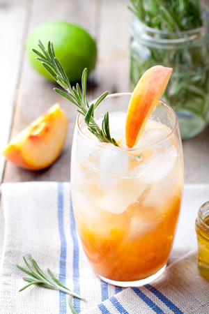 water thyme: Peach and rosemary fizz cocktail on a wooden background.