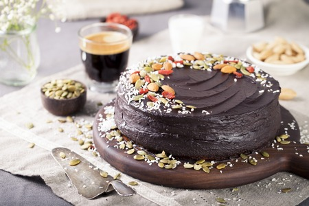 Vegan chocolate beet cake with avocado frosting, decorated with nuts and seeds Stock Photo