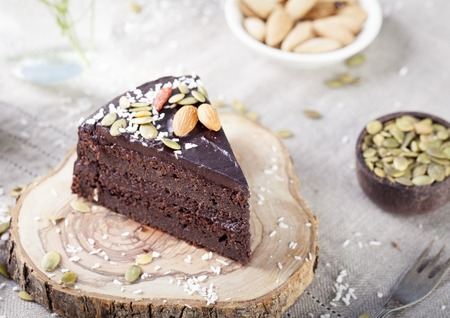 Vegan chocolate beet cake with avocado frosting, decorated with nuts and seeds Stockfoto