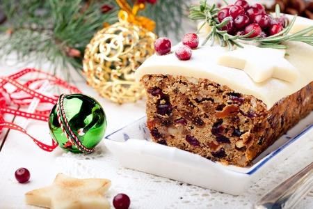 Traditionele kerst Fruit Cake pudding met marsepein en cranberry en rozemarijn decor op een kerstversiering achtergrond