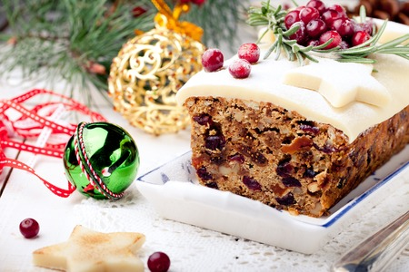 Traditional Christmas Fruit Cake pudding with marzipan and cranberry and rosemary decor on a Christmas decoration background Standard-Bild