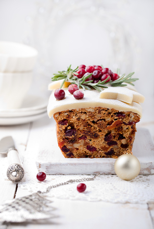 rum cake: Traditional Christmas Fruit Cake pudding with marzipan and cranberry and rosemary decor on a Christmas decoration background Stock Photo