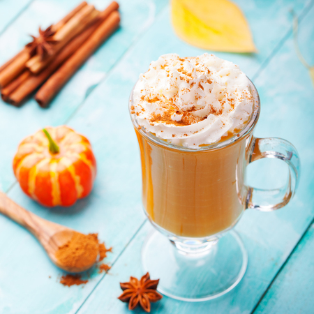 spice: Pumpkin smoothie, spice latte with whipped cream on top on a turquoise wooden background. copy space