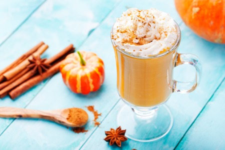Pumpkin smoothie, spice latte with whipped cream on top on a turquoise wooden background. copy space
