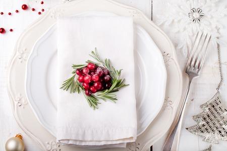 Kerstmis en Nieuwjaar Holiday tabel met cranberry en rozemarijn decoratie. Vakantie decoratie.