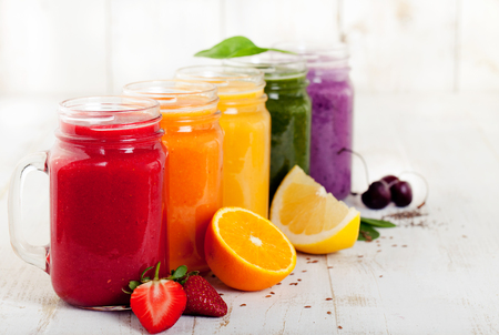 batidos de frutas: Variedad batidos, zumos, bebidas, bebidas con frutas frescas y frutas sobre un fondo de madera blanca