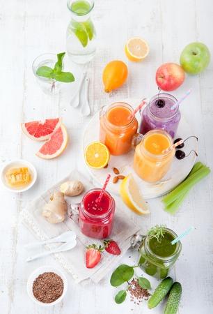 Strawberry smoothie: Frullati, succhi di frutta, bevande, bevande varietà con frutta fresca e bacche su uno sfondo bianco di legno. Vista dall'alto.