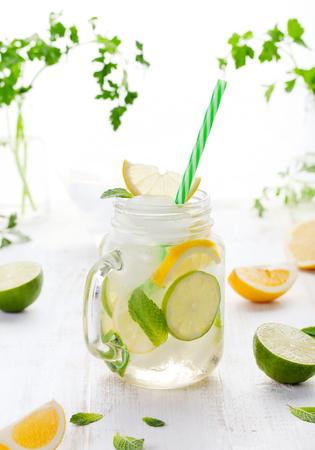 Limonade met ijs, citroen en limoen plakjes in een pot met stro op een witte zomer houten achtergrond