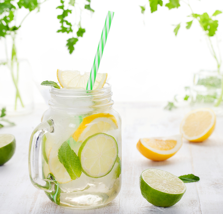 lemon water: Lemonade with ice, lemon and lime slices in a jar with straw in a white summer wooden background