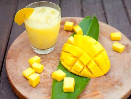Mango sap, smoothie en mango fruit op een houten achtergrond