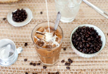 Traditional Vietnamese, Thai Ice coffee with coffee beans on a wooden background