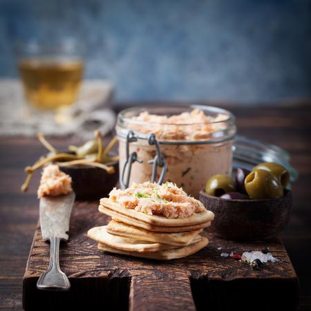 Salmón ahumado y queso para untar suave, mousse, paté en un frasco con galletas saladas, aceitunas y alcaparras sobre un fondo de madera
