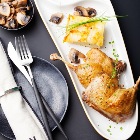 Duck legs confit with potato gratin and mushroom sauce Stock Photo