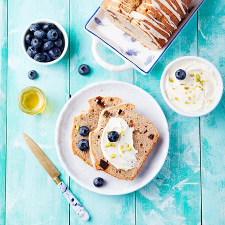 comiendo platano: Pan de pl�tano con crema de vainilla crema de queso, miel, bayas frescas ar�ndanos en un fondo azul turquesa de madera Foto de archivo