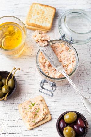 queso: Salm�n ahumado y queso para untar suave, mousse, pat� en un frasco con galletas saladas, aceitunas y alcaparras sobre un fondo de madera