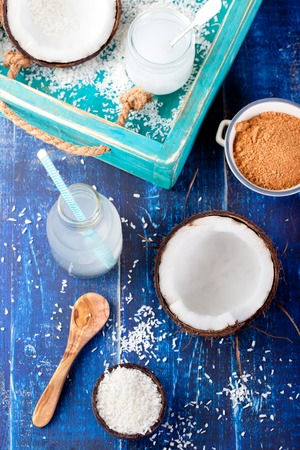 coconut palm sugar: Coconut with coconut oil, water and sugar and coconut flakes on a wooden turquoise background