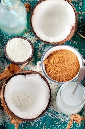 Kokosnoot met kokosolie, water en suiker en kokos vlokken op een houten turkooise achtergrond
