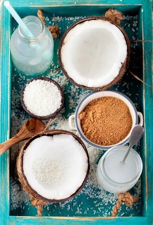 aceite de coco: Coco con aceite de coco, el agua y el az�car y coco copos sobre un fondo de color turquesa de madera