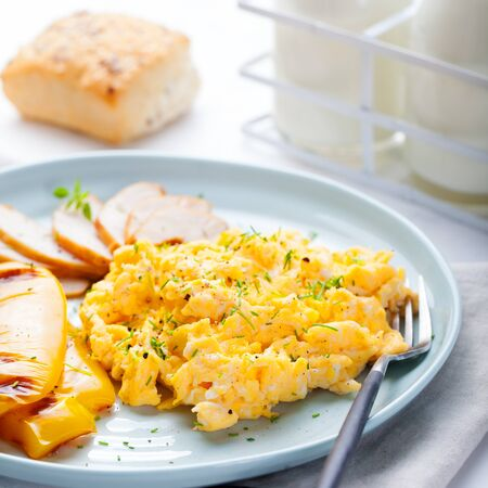 green: Scrambled eggs, omelet with grilled bell sweet pepper and hot smocked chicken, ham in a plate with a cup of coffee and bread on a white background