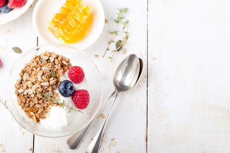 muesli: Granola with pumpkin seeds, honey, yogurt and fresh berries in a ceramic bowl on white background.