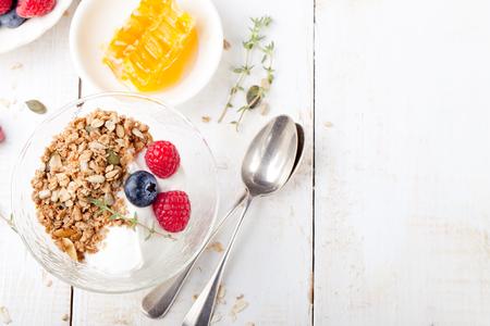 Muesli con semi di zucca, miele, yogurt e frutti di bosco freschi in una ciotola in ceramica su sfondo bianco. Archivio Fotografico - 47435536