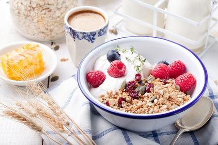 Muesli met pompoenpitten, honing, yoghurt en verse bessen in een keramische kom op een witte achtergrond.