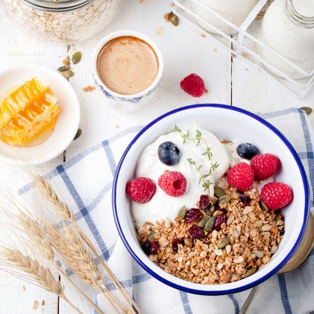 Granola with pumpkin seeds, honey, yogurt and fresh berries in a ceramic bowl on white background. Stock Photo - 47435511