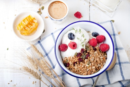 Granola with pumpkin seeds, honey, yogurt and fresh berries in a ceramic bowl on white background.