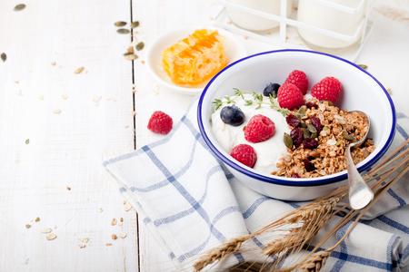 breakfast: Granola con semillas de calabaza, miel, yogur y bayas frescas en un recipiente de cerámica en el fondo blanco.