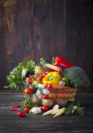 canastas con frutas: Verduras variedad en una cesta de alambre sobre un fondo de madera Foto de archivo