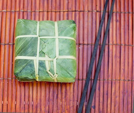 leaf vegetable: Banh chung, Traditional present for Lunar New Year, Vietnamese traditional dish. Sticky rice cake with meat, covered with banana leaves and, tied with bamboo rope