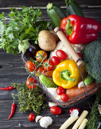 fruits in a basket: Vegetables variety in a wire basket on a wooden background.