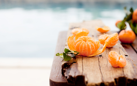 eating fruits: Fresh tangerines on a wooden table on a blue, sea, water background
