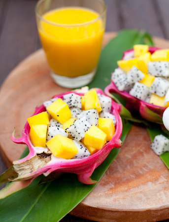 thai dessert: Tropical fruit salad in pitahaya, dragon fruit bowls with a glass of mango juice and flower on a wooden background