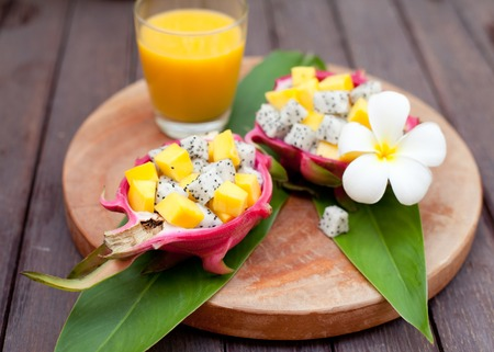 Tropical fruit salad in pitahaya, dragon fruit bowls with a glass of mango juice and flower on a wooden background
