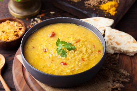yellow: Red lentil Indian soup with flat bread on a wooden background. Masoor dal.
