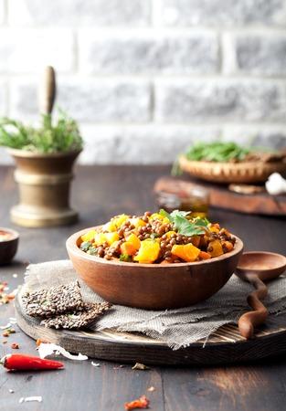 Linzen met wortel en pompoen ragout in een houten kom op een houten achtergrond