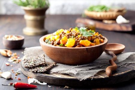 zanahoria: Lentejas con zanahoria y ragout de calabaza en un cuenco de madera sobre un fondo de madera