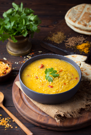 ensalada: Red lentil Indian soup with flat bread on a wooden background. Masoor dal.
