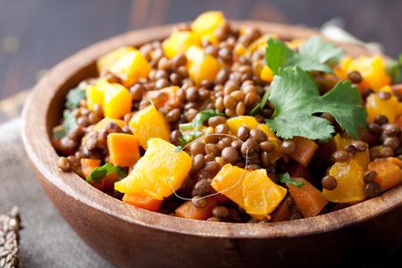 나무 배경에 나무 그릇에 당근과 호박 스튜 요리의 일종으로 렌즈 콩