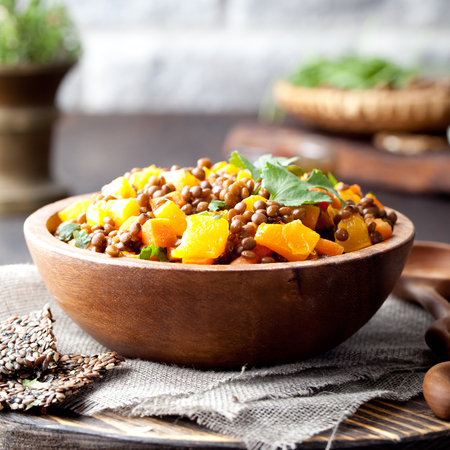 Lentil with carrot and pumpkin ragout in a wooden bowl on a wooden background