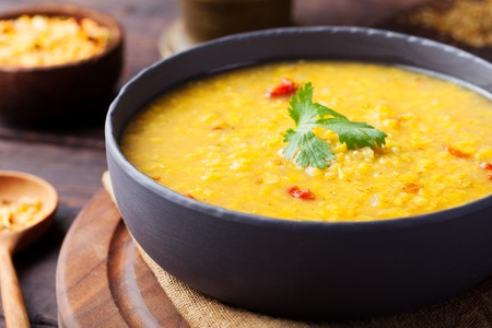 hot soup: Red lentil Indian soup with flat bread on a wooden background. Masoor dal.