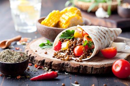 bocadillo: Envoltura vegano tortilla, rollo con vegetabes la parrilla y la lenteja y la mazorca de maíz hervida en un fondo de madera