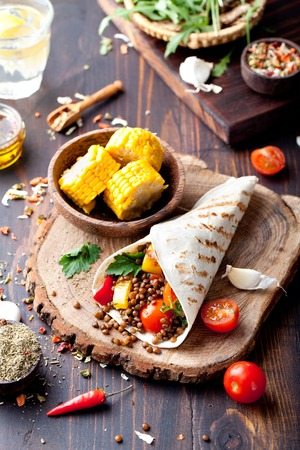 burrito: Vegan tortilla wrap, roll with grilled vegetabes and lentil and boiled corn cob on a wooden background