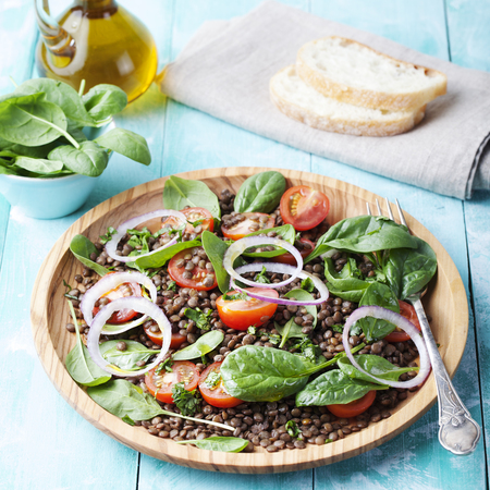 Lentil salad with cherry tomatoes, red onion and baby spinach in a wooden plate on a turquoise background