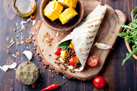 grilled vegetables: Vegan tortilla wrap, roll with grilled vegetabes and lentil and boiled corn cob on a wooden background