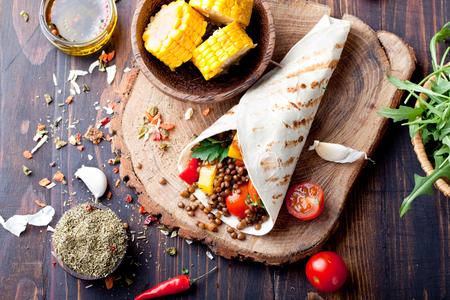 Vegan tortillaomslag, roll met gegrilde vegetabes en linzen en gekookte maïskolf op een houten achtergrond Stockfoto
