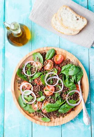 Linzen salade met cherry tomaten, rode ui en baby spinazie in een houten plaat op een turkooise achtergrond Stockfoto
