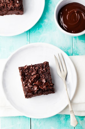 brownies: Chocolate brownie, cake on a white plate on a turquoise wooden background