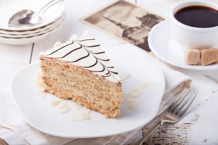 compleanno: Traditional Hungarian Esterhazy cake with coffee cup and vintage postcards on a white wooden background.